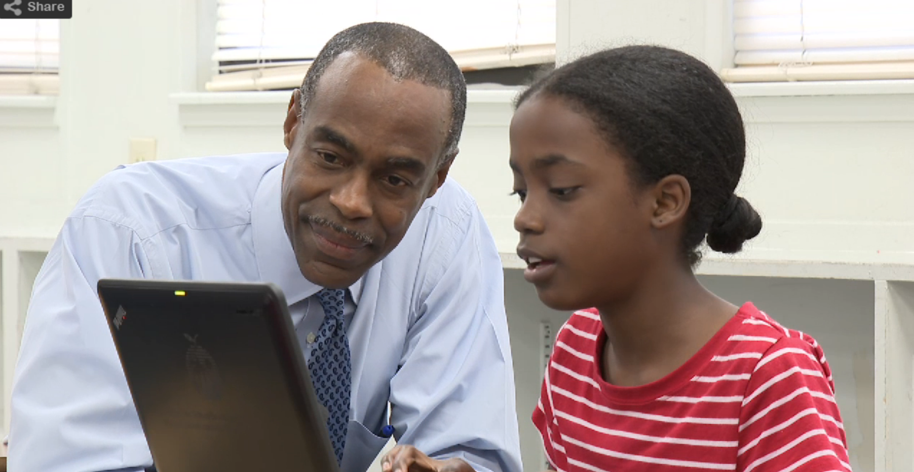 Superintendent Runcie with a student looking at a laptop