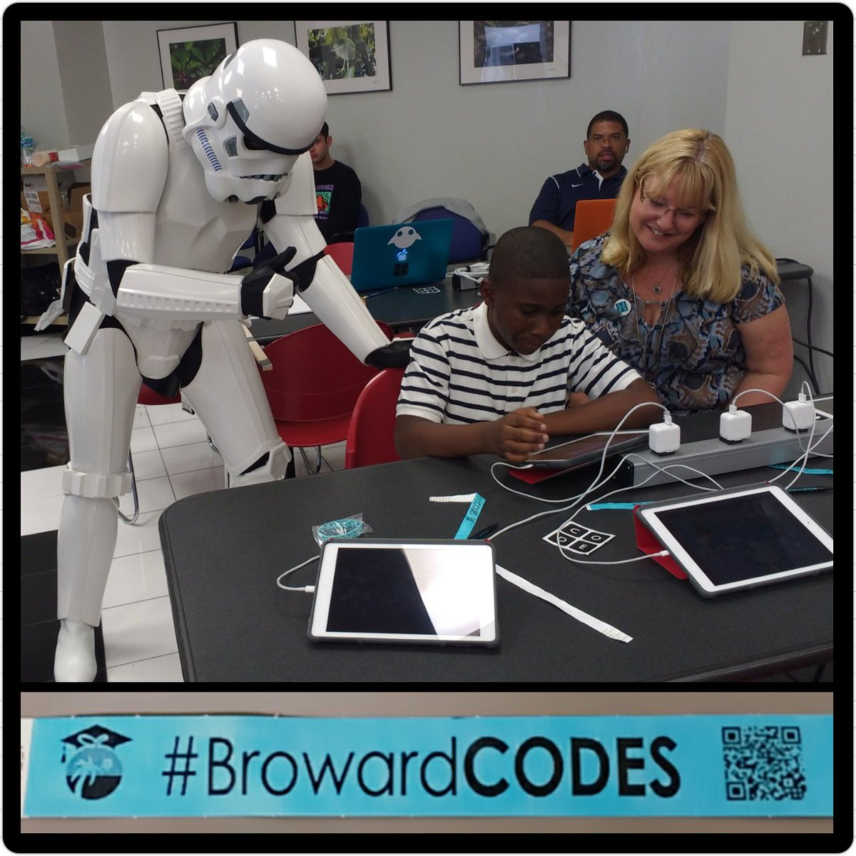 Stormtrooper and female teacher looking over student with laptop