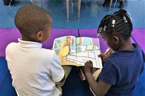 Two students reading a book.