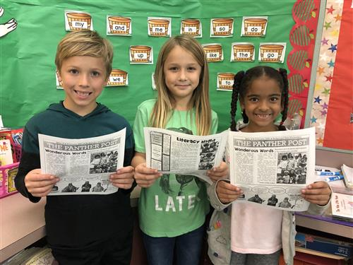 students reading newsletter