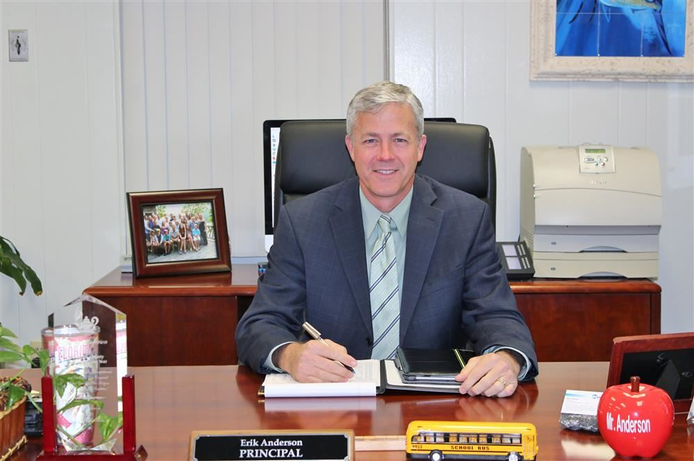 Principal Robert Schneider  sitting at his desk.