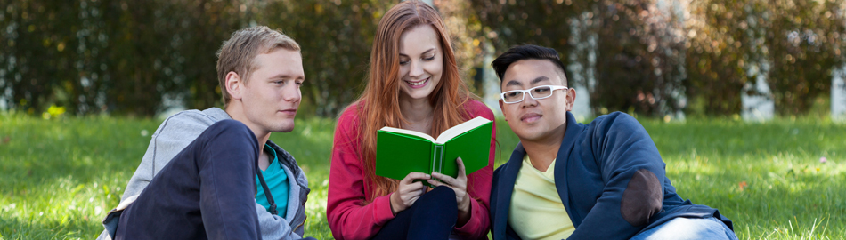 Young lady reading a book to two young men outside