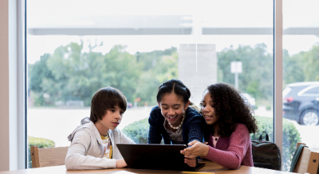 Three students reviewing legal information on a computer