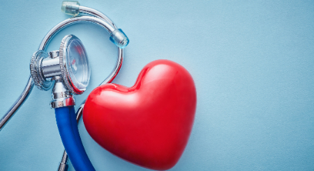 A red heart and a blue stethoscope on a table