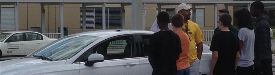 Driver's Ed teacher speaking to students near white driver's ed car